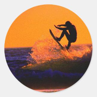 Persona que practica surf de la puesta del sol pegatina redonda