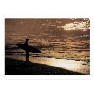Persona que practica surf de la salida del sol postal