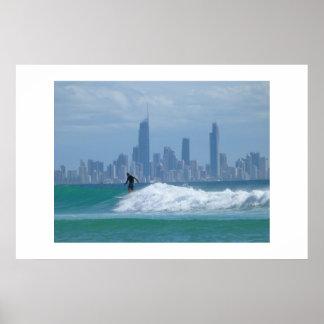 Persona que practica surf delante de los rascaciel póster