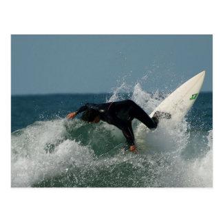 Persona que practica surf en playa del océano postales