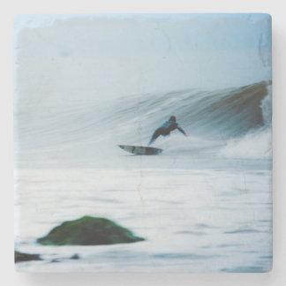 Persona que practica surf posavasos de piedra