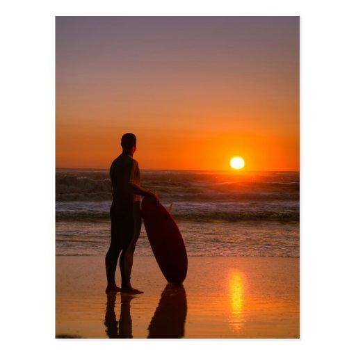 Persona que practica surf que mira las ondas postales