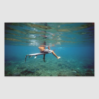 Persona que practica surf que se sienta en el filó rectangular altavoz