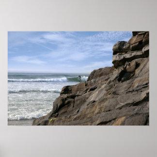 persona que practica surf solitaria cerca de rocas poster