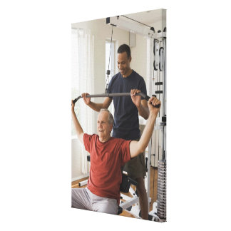 Personal trainer with man in home gym stretched canvas prints