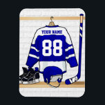 "Personalized Blue and White Ice Hockey Jersey Magnet<br><div class=""desc"">A personalized ice hockey jersey in blue and white hanging in a sports locker room with a helmet, ice skates and an ice hockey stick. The jersey can be fully customized with the number and name of your choice to make a great gift for the ice hockey fan, ice hockey...</div>"
