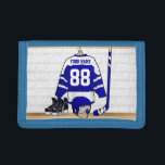 """Personalized Blue and White Ice Hockey Jersey Tri-fold Wallet<br><div class=""""desc"""">A personalized ice hockey jersey in blue and white hanging in a sports locker room with a helmet, ice skates and an ice hockey stick. The jersey can be fully customized with the number and name of your choice to make a great gift for the ice hockey fan, ice hockey...</div>"""