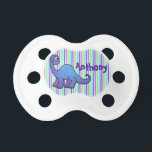 """Personalized Dinosaur on Stripes Pacifier<br><div class=""""desc"""">This cute and special custom baby pacifier for a little boy has a friendly, smiling blue and purple dinosaur on a multi-color striped background in shades of purple, green, and aqua blue. You can personalize the purple text with a name, initials, or other text. If you need assistance with anything,...</div>"""