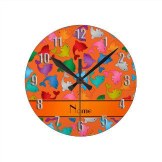 Personalized name orange rainbow dolphins round clock