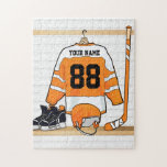 """Personalized Orange and White Ice Hockey Jersey Jigsaw Puzzle<br><div class=""""desc"""">An ideal gift for the ice hockey fan, ice hockey player or ice hockey coach, this design features a personalized ice hockey jersey in orange and white hanging in a sports locker room with a helmet, ice skates and an ice hockey stick. The jersey can be fully customized with the...</div>"""