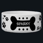 """Personalized paw prints and dog bone pet food bowl<br><div class=""""desc"""">This ceramic dog food bowl has lots of little black paw prints and polka dots everywhere.  In the middle,  there is a large black bone with an easily customized name of your doggie.</div>"""