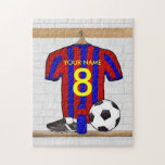 "Personalized Red and Blue Football Soccer Jersey Jigsaw Puzzle<br><div class=""desc"">Add the name and number or age of the soccer player, football fan or soccer team coach to this unique sports design featuring a red and blue striped football soccer jersey hanging in the locker room. There is a water bottle, a soccer ball and football cleats on the bench under...</div>"
