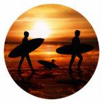 Personas que practica surf de la puesta del sol escultura fotografica