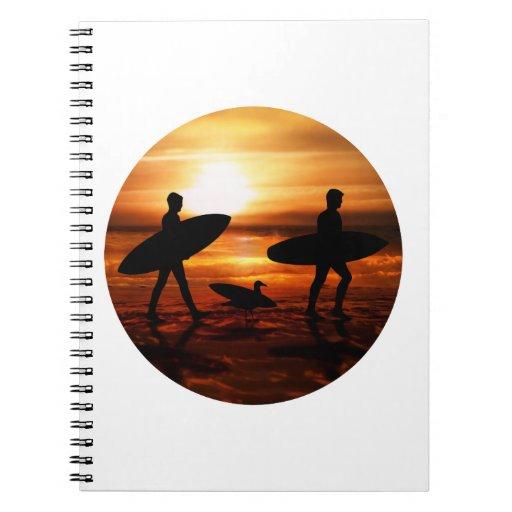 Personas que practica surf de la puesta del sol libreta