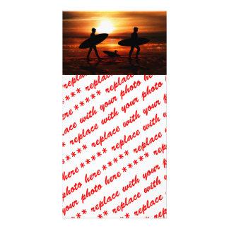 Personas que practica surf de la puesta del sol tarjeta fotografica