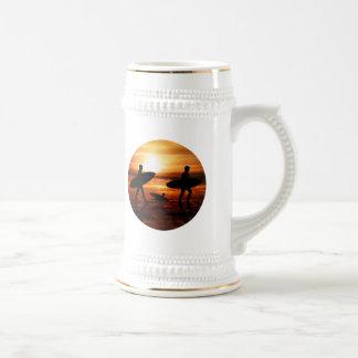 Personas que practica surf de la puesta del sol taza de café