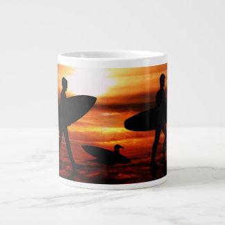 Personas que practica surf de la puesta del sol taza grande
