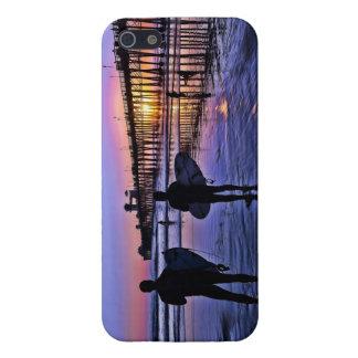 Personas que practica surf en la puesta del sol iPhone 5 fundas