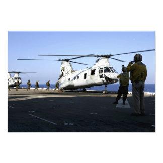 Personnel walk into the rear of a CH-46E Photo Print