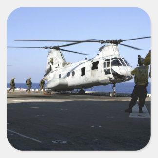 Personnel walk into the rear of a CH-46E Square Sticker