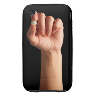 Persons hand holding a white pill between the iPhone 3 tough covers