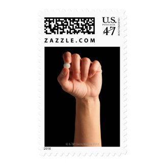 Persons hand holding a white pill between the postage