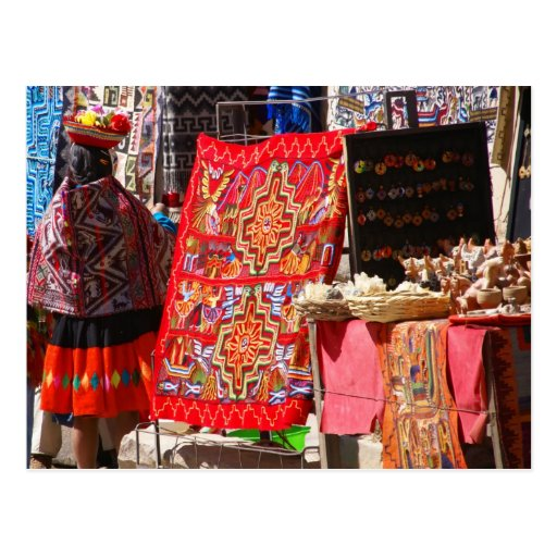 Peruvian Indian woman looking at colorful textiles Post Cards
