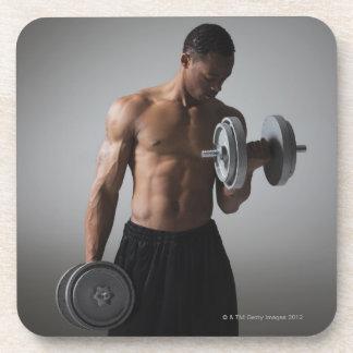 Pesas de gimnasia de elevación del hombre muscular posavasos de bebida