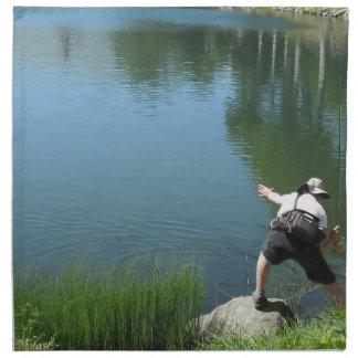 Pesca con mosca del hombre en un lago de la servilletas