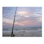 Pesca de la playa en la puesta del sol tarjetas postales