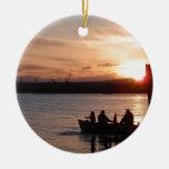 Pesca que va en la puesta del sol adornos
