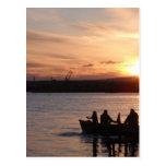 Pesca que va en la puesta del sol postal