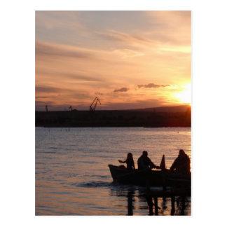 Pesca que va en la puesta del sol postales