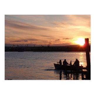 Pesca que va en la puesta del sol tarjetas postales