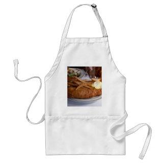 Pescado frito con patatas fritas con una pinta de  delantal