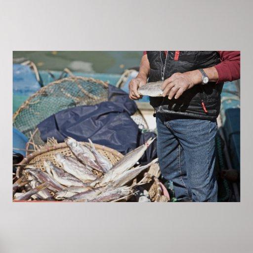 Pescador local con una cesta de pescados póster
