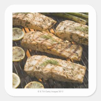 Pescados y espárrago que cocinan en parrilla pegatina cuadrada