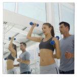 Pesos de elevación de la mujer con el instructor azulejo cuadrado grande