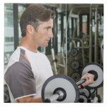 Pesos de elevación del hombre en el gimnasio 2 azulejo cuadrado grande