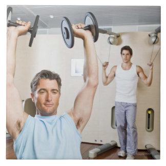 Pesos de elevación del hombre en el gimnasio azulejo cuadrado grande