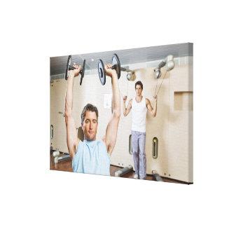 Pesos de elevación del hombre en el gimnasio lona envuelta para galerias
