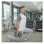 Pesos de elevación del hombre en gimnasio azulejo cuadrado grande