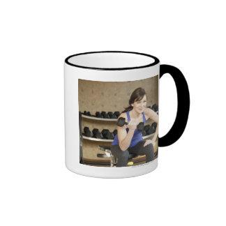 Pesos de elevación femeninos activos en un privado taza de café