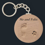 "Pet &amp; Footprint in the Sand Keychain<br><div class=""desc"">A gift from the pet to the owner, a memory gift for a pet who died, or a great gift for the pet owner. This pet gift features a human footprint and pet paw print side-by-side in the sand. Very unique design to honor your pet is available on this product...</div>"