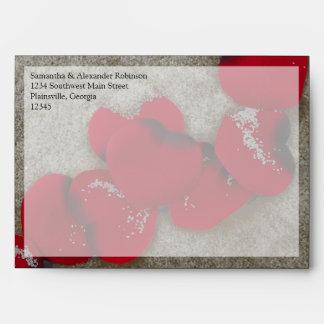 Pétalos color de rosa rojos en el boda de playa de sobre