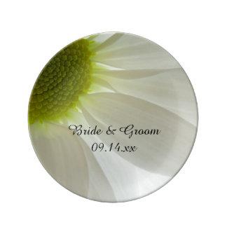Pétalos de la margarita blanca que casan el plato de cerámica