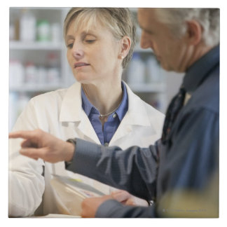 Pharmacist helping customer with medicine tile
