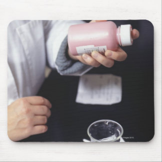 Pharmacist holding medicine bottle, close-up, mouse pad