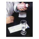 Pharmacist holding medicine bottle, close-up, postcard