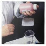 Pharmacist holding medicine bottle, close-up, large square tile